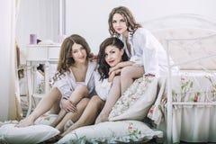 Tres amigos hermosos de las mujeres jovenes que charlan en el dormitorio adentro Fotos de archivo