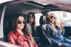 Tres amigos hermosos de las mujeres jovenes se divierten en el coche de o mientras que van en un viaje por carretera Fotos de archivo libres de regalías