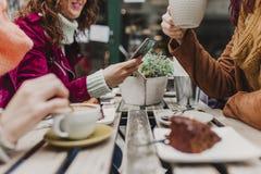 Tres amigos irreconocibles de las mujeres que comen café en una terraza en Oporto, Portugal Tener una conversación de la diversió fotos de archivo