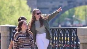 Tres amigos jovenes que caminan en el puente en Praga metrajes