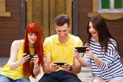 Tres amigos jovenes que ríen el vídeo de observación en outd del teléfono móvil foto de archivo