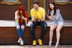 Tres amigos jovenes que ríen jugando al videojuego móvil al aire libre fotos de archivo