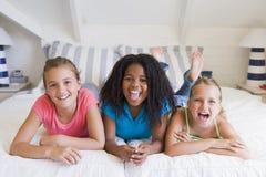 Tres amigos jovenes que se acuestan al lado de uno a Fotografía de archivo