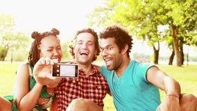 Tres amigos jovenes que se divierten que toma selfies almacen de metraje de vídeo