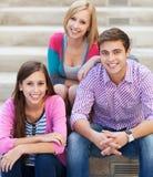 Tres amigos jovenes que se sientan junto Imagen de archivo