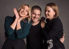 Tres amigos jovenes que se unen, abrazando, riendo y sonriendo El estudio tirado en la pared gris Fotos de archivo