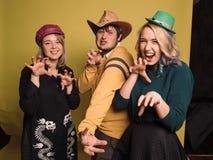 Tres amigos jovenes que se unen, bailando, riendo y sonriendo El estudio tirado en la pared amarilla Fotos de archivo libres de regalías