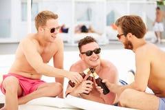 Tres amigos masculinos jovenes el día de fiesta por la piscina junto Imágenes de archivo libres de regalías