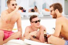 Tres amigos masculinos jovenes el día de fiesta por la piscina junto Imagen de archivo
