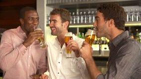 Tres amigos masculinos que disfrutan de la bebida en la barra almacen de video