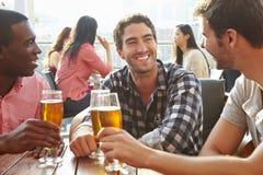 Tres amigos masculinos que disfrutan de la bebida en la barra al aire libre del tejado Foto de archivo
