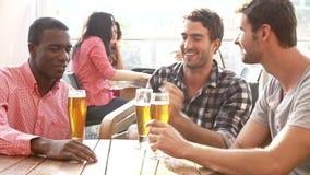 Tres amigos masculinos que disfrutan de la bebida en la barra al aire libre del tejado almacen de video