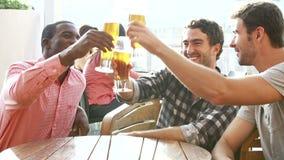 Tres amigos masculinos que disfrutan de la bebida en la barra al aire libre del tejado metrajes
