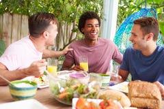 Tres amigos masculinos que disfrutan de la comida al aire libre en casa Imágenes de archivo libres de regalías