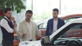 Tres amigos masculinos que examinan el coche para la venta en la representación metrajes