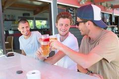 Tres amigos masculinos relajan la cerveza de consumición hacia fuera en terraza del restaurante Foto de archivo