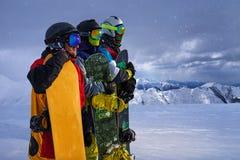 Tres amigos miran a snowboarders delanteros valeroso imagenes de archivo