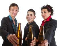 Tres amigos partying con la cerveza Imágenes de archivo libres de regalías