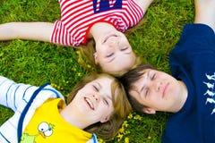 Tres amigos puestos en una hierba Imagen de archivo
