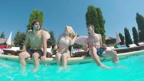 Tres amigos que bailan y que se divierten al borde de una piscina metrajes