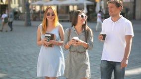 Tres amigos que beben el café y que caminan alrededor de la ciudad durante día caliente del verano Dos muchachas que llevan las g metrajes