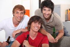 Tres amigos que beben la cerveza Foto de archivo libre de regalías
