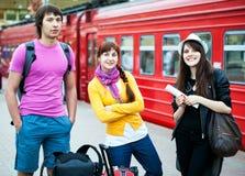 Tres amigos que esperan un tren en la estación Fotos de archivo