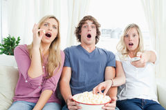 Tres amigos que gozan de las palomitas juntas mientras que está chocado en la TV Fotos de archivo libres de regalías