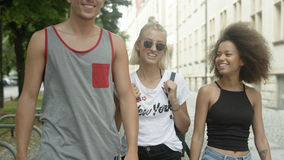 Tres amigos que hablan el uno al otro como ellos que caminan junto en una ciudad Fotografía de archivo
