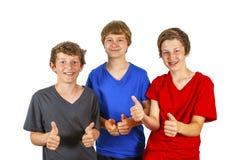 Tres amigos que hacen thumbs-up y la como-él-muestra Fotografía de archivo