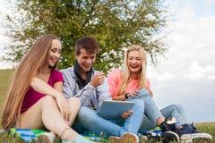 Tres amigos que juegan al juego en la PC de la tableta Ellos que ganan otra vez Fotos de archivo libres de regalías