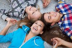 Tres amigos que mienten en círculo Foto de archivo libre de regalías