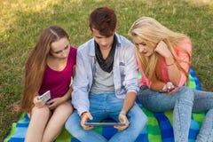 Tres amigos que miran películas divertidas en la PC de la tableta en parque Fotografía de archivo libre de regalías