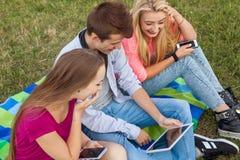 Tres amigos que miran películas divertidas en la PC de la tableta en parque Fotos de archivo libres de regalías