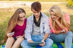 Tres amigos que miran películas divertidas en la PC de la tableta en parque Imagenes de archivo