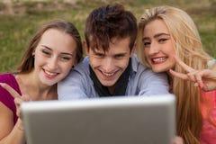 Tres amigos que miran tomando imágenes con PC de la tableta en parque Foto de archivo libre de regalías