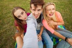 Tres amigos que miran tomando imágenes con PC de la tableta en parque Imagen de archivo