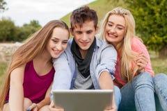 Tres amigos que miran tomando imágenes con PC de la tableta en parque Fotografía de archivo