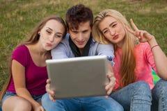Tres amigos que miran tomando imágenes con PC de la tableta en parque Fotografía de archivo libre de regalías