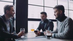 Tres amigos que pasan el tiempo junto en el pub, el hombre en el traje muestran el smth en su teléfono, todos están satisfechos c almacen de metraje de vídeo