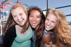 Tres amigos que ríen junto Imagenes de archivo