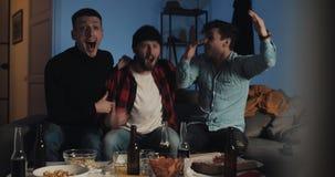 Tres amigos que ruegan mientras que partido de fútbol de observación en la televisión en casa, animando al mejor equipo de fútbol metrajes