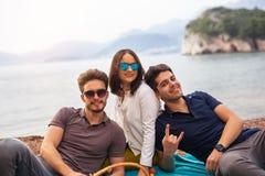 Tres amigos que se divierten en la playa Imagen de archivo libre de regalías