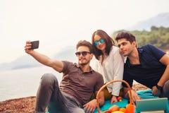 Tres amigos que se divierten en la playa, hacen el selfie Foto de archivo libre de regalías
