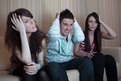 Tres amigos que se sientan en el sofá fotografía de archivo
