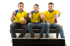 Tres amigos que se sientan en el sofá que lleva las camisas de deportes amarillas que miran la televisión con el entusiasmo, fond Imagen de archivo