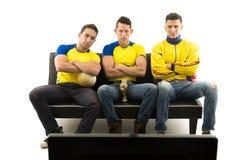 Tres amigos que se sientan en el sofá que lleva las camisas de deportes amarillas que miran la televisión con expresiones faciale Imagen de archivo libre de regalías
