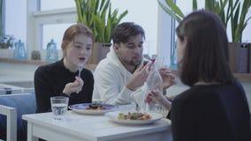 Tres amigos que se sientan en restaurante, charlando y sonriendo durante tomar platos delisious en almuerzo en lugar acogedor almacen de video