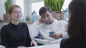 Tres amigos que se sientan en un café o un eje, charlando y sonriendo durante la rotura, mientras que el esperar del SMS del indi almacen de metraje de vídeo