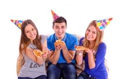 Tres amigos que se sientan en un sofá y que comen la pizza Foto de archivo libre de regalías